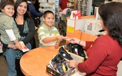 A family shopping for Payless shoes with a voucher from the retailers charity program
