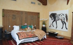 Handwoven rugs decorate the floor of the master bedroom where tribal drums serve as nightstands