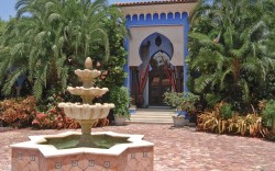 The gated driveway leads to a courtyard with a working fountain and parking space for 15 cars