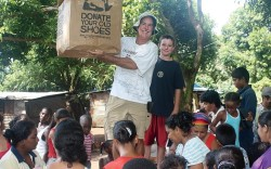 Philip Cleary handing out shoes to women and children