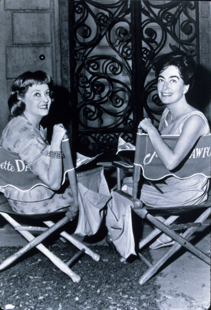 """Bette Davis (L) and Joan Crawford (R) flash smiles on the set of """"Whatever Happened to Baby Jane?"""""""