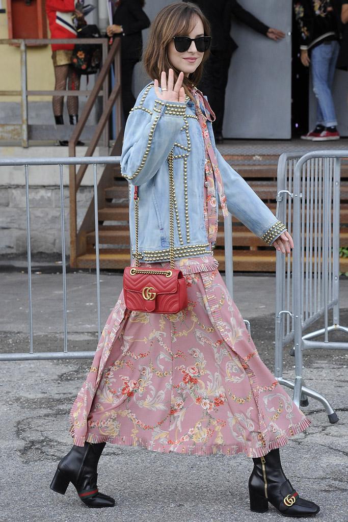 Dakota Johnson during Milan Fashion Week wearing Gucci leather ankle boots.