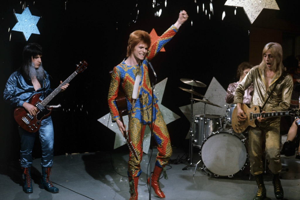 David Bowie performing as Ziggy Stardust, with Trevor Bolder and Mick Ronson in 1972.