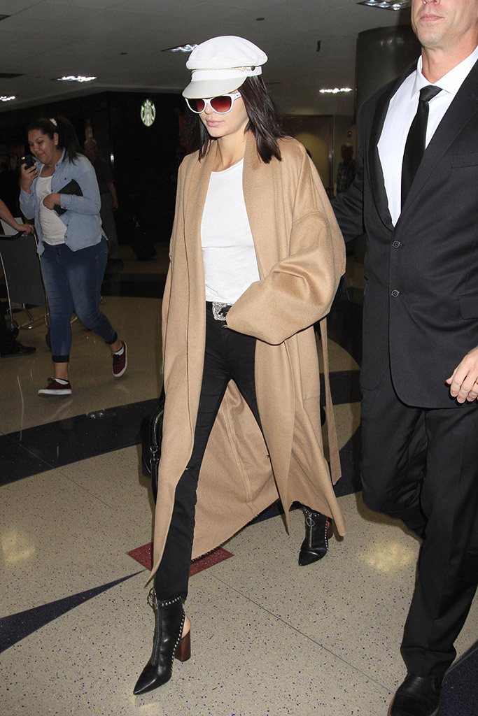 Kendall Jenner looks amazing as she arrives in LA after her steamy Miami photo shoot. The leggy KUWTK model was seen wearing bla k jeans, studded boots, a white tee-shirt, a cap & a long beige coat. Pictured: Kendall JennerRef: SPL1460201 130317 Picture by: Sharky/Polite Paparazzi/SPLASHSplash News and PicturesLos Angeles:310-821-2666New York:212-619-2666London:870-934-2666photodesk@splashnews.com