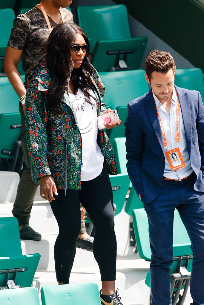 Serena Williams wears floral jacket with white Nike tank top and black Nike sneakers