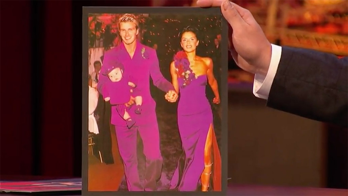 James Corden holds up a picture of David and Victoria Beckham in coordinated purple looks at their wedding reception in 1999