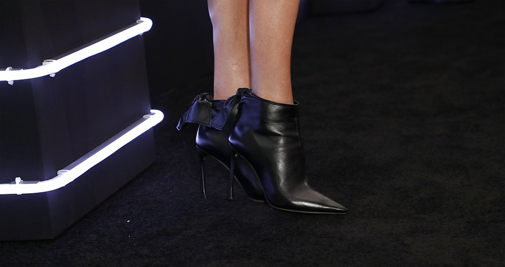 A close-up of Charlize Theron's leather booties with bow details.