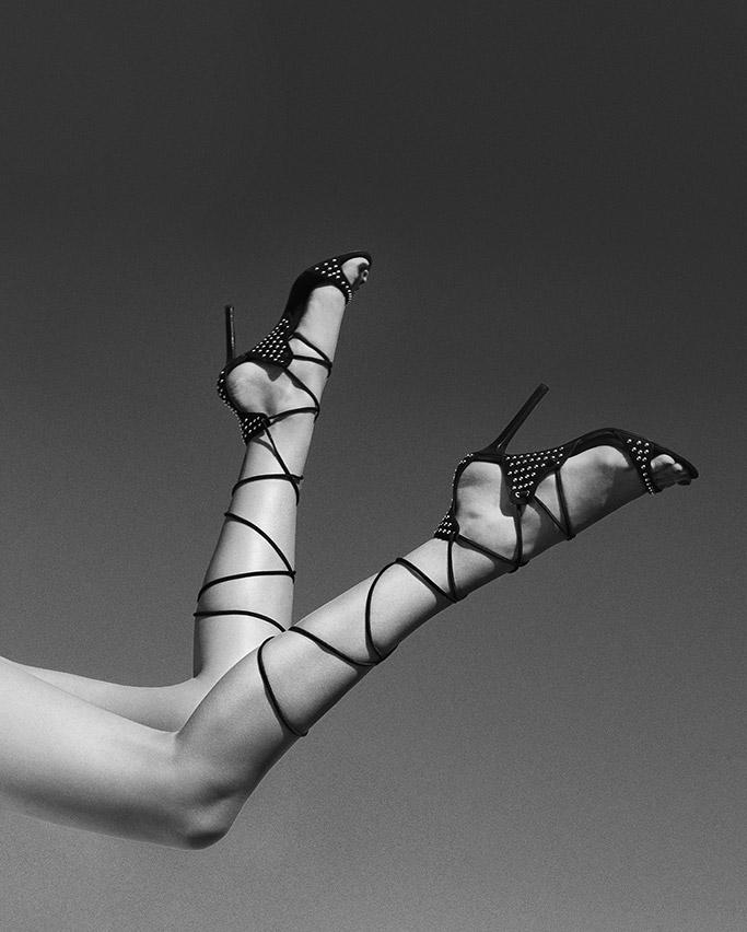 A model wears the Tamara Mellon Matrix 105 sandal in black suede.