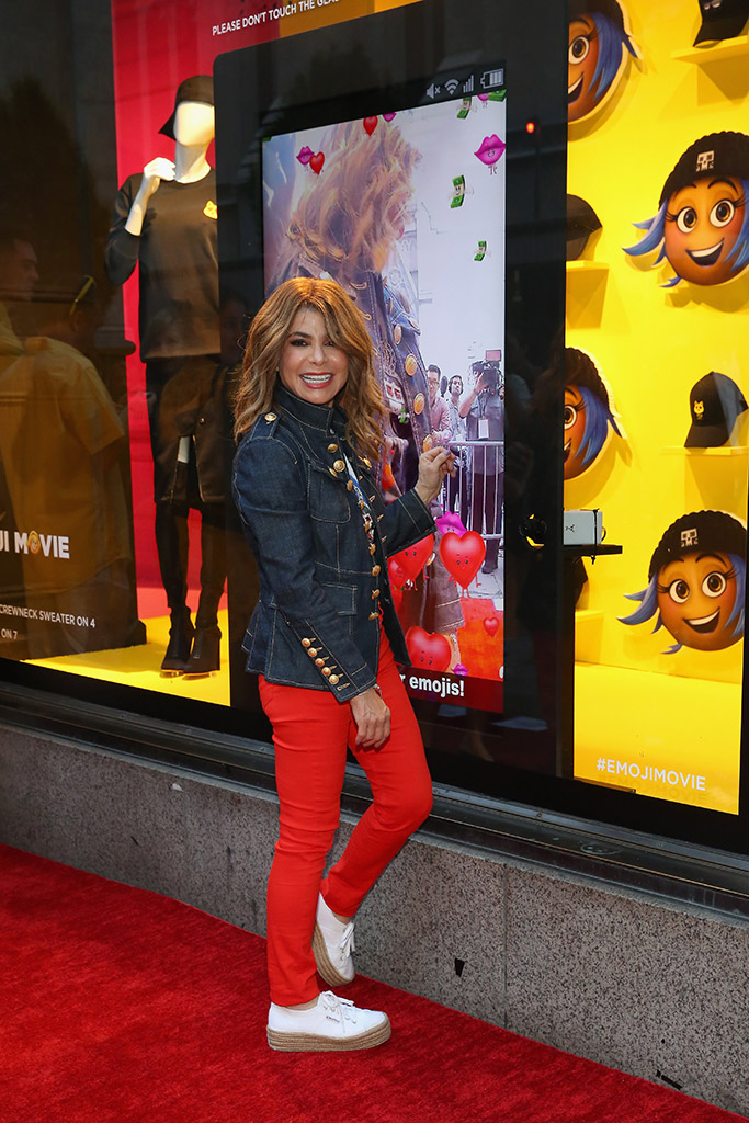 Paula Abdul plays with the interactive window technology created by Mitene & Sony Music Communications on the red carpet at the saks fifth avenue x emoji movie collection.