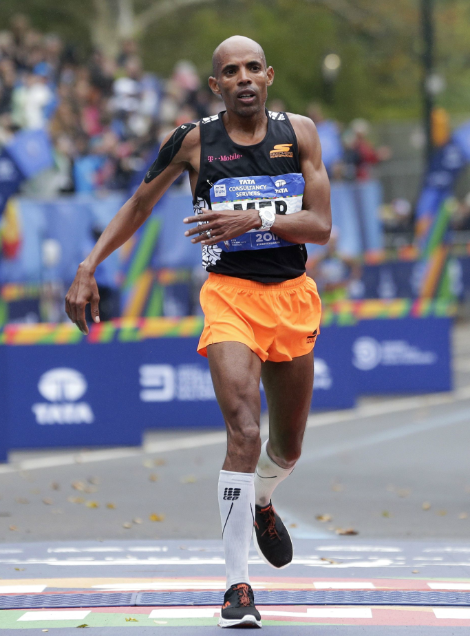 Meb Keflezighi crosses the finish line wearing black and orange Skechers sneakers