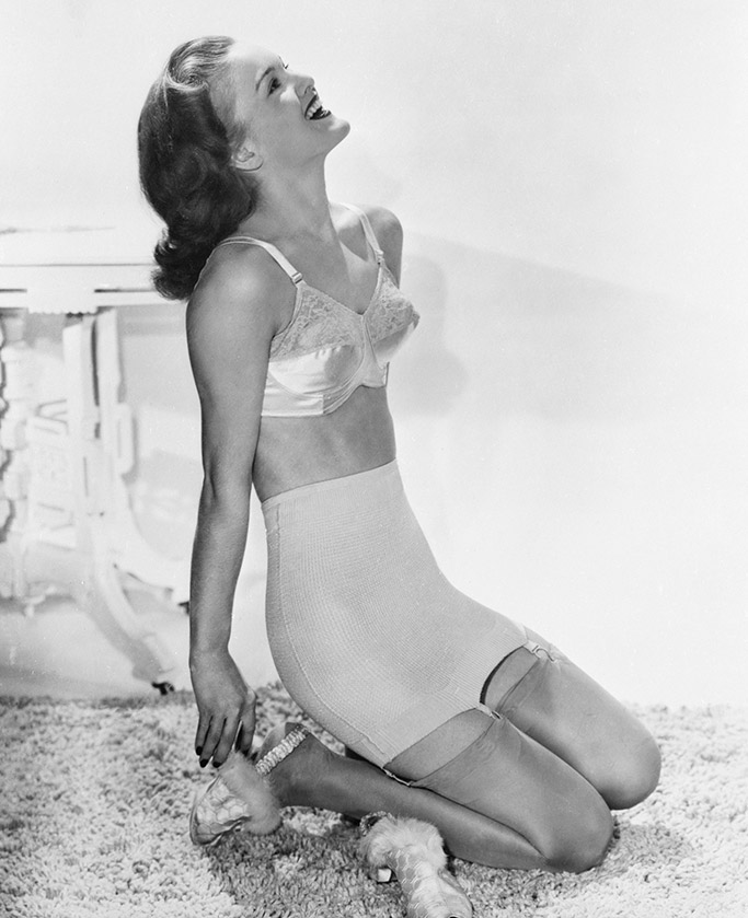 a 1940s photograph of a woman wearing a girdle and bullet bra