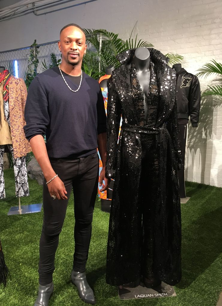 Fashion designer LaQuan Smith stands with his jumpsuit and trench coat created for a small collection inspired by the film
