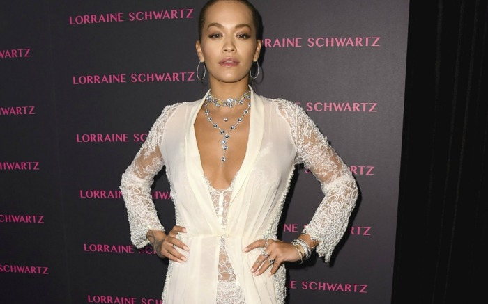 Rita Ora covers up her revealing white look.