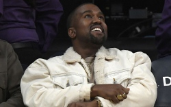 Rapper Kanye West watches during the