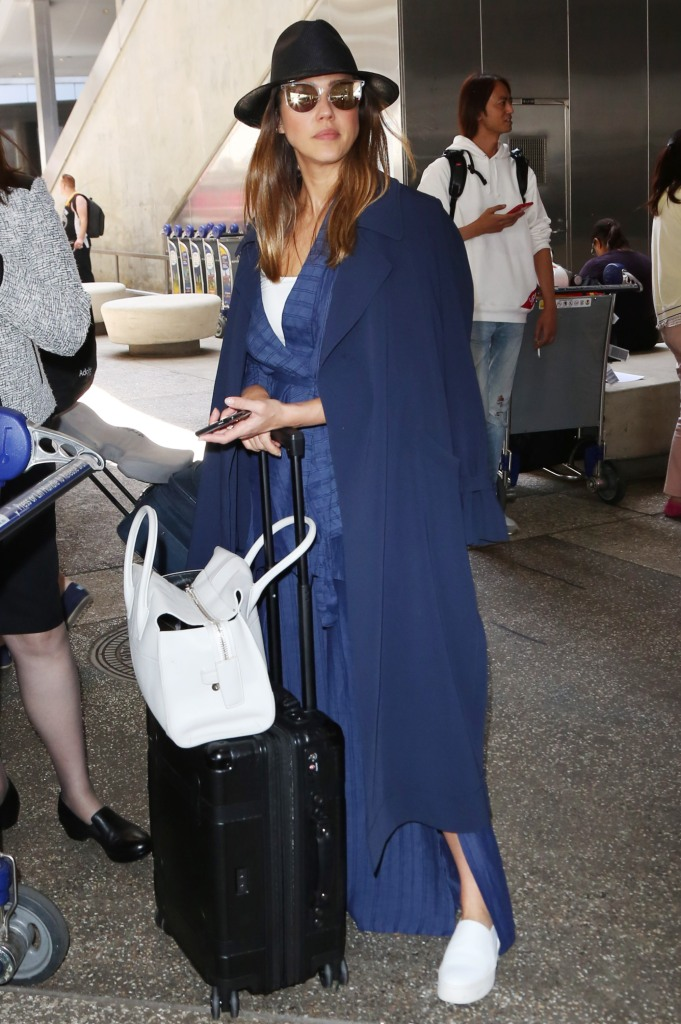 Jessica Alba arrives at the LAX international airport wearing a navy and white look.