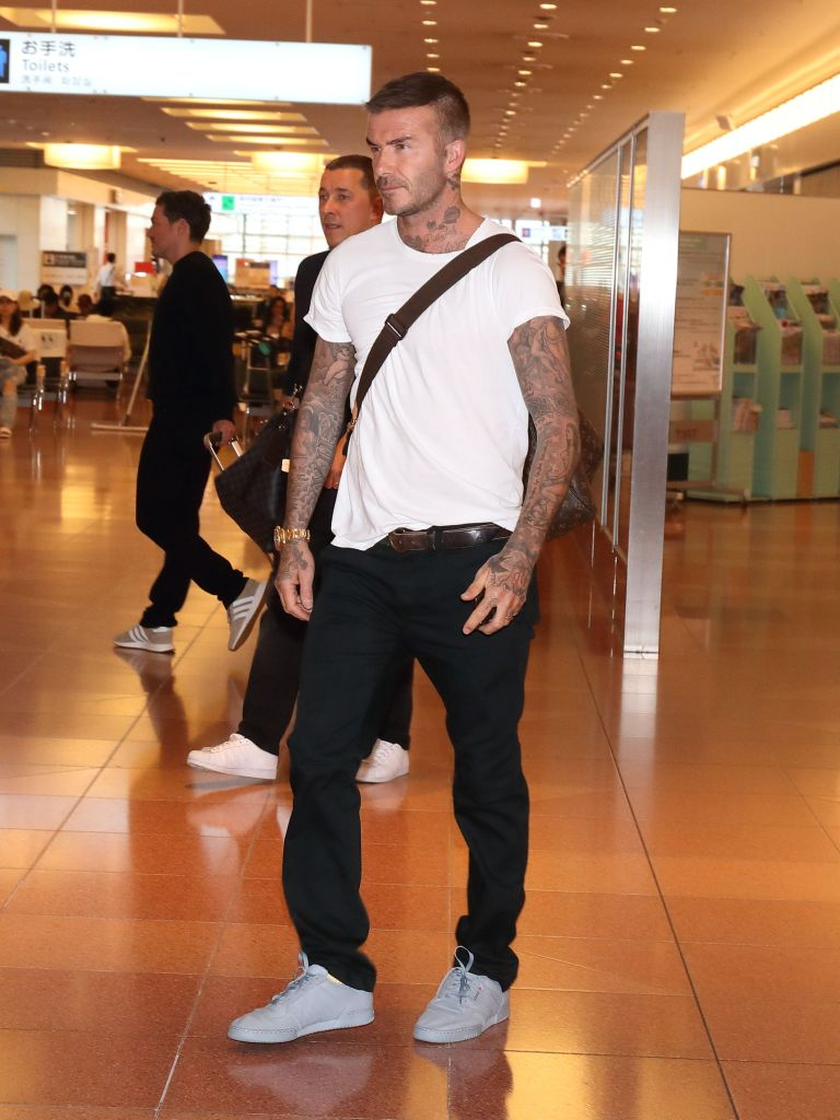 David Beckham had on a clean white tee, dark jeans and gray Yeezy sneakers at Tokyo's Haneda international airport.