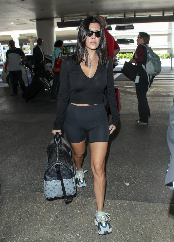 Kourtney Kardashian seen wearing Yeezys and holding onto a Louis Vuitton duffel bag at the LAX international airport.