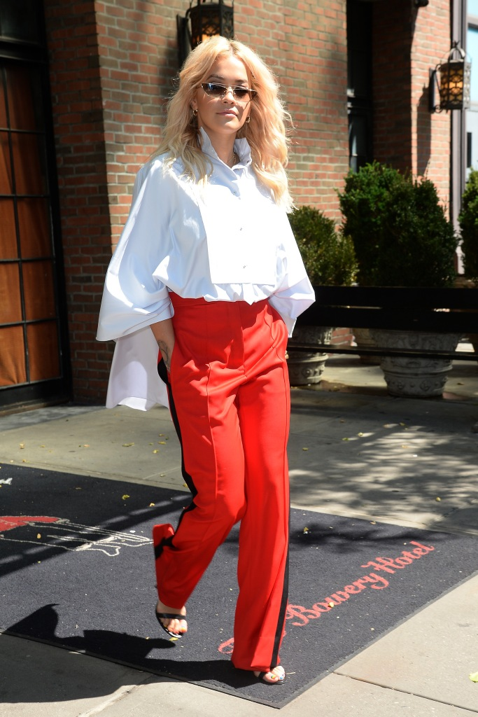 A snapshot of Rita Ora's red and black wide legged pants and loose cape-like white button down top.