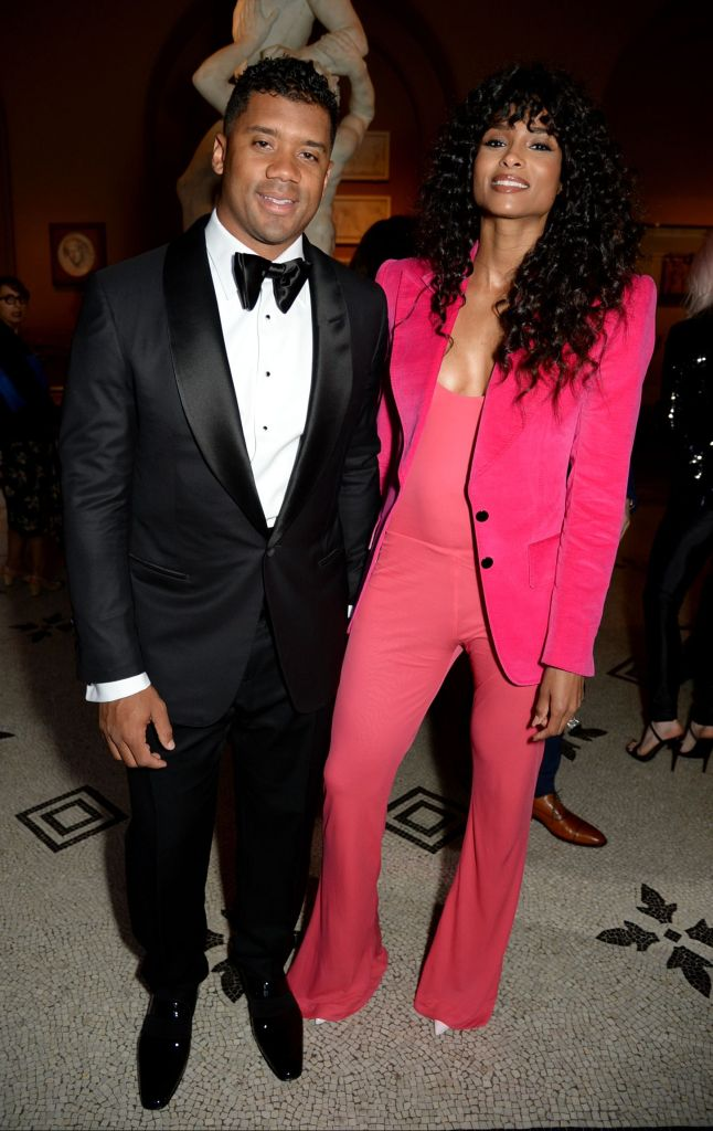 Russell Wilson looked dapper in black and white tuxedo alongside wife Ciara as she wore a hot pink pant suit at the Victoria and Albert Museum summer party in London.