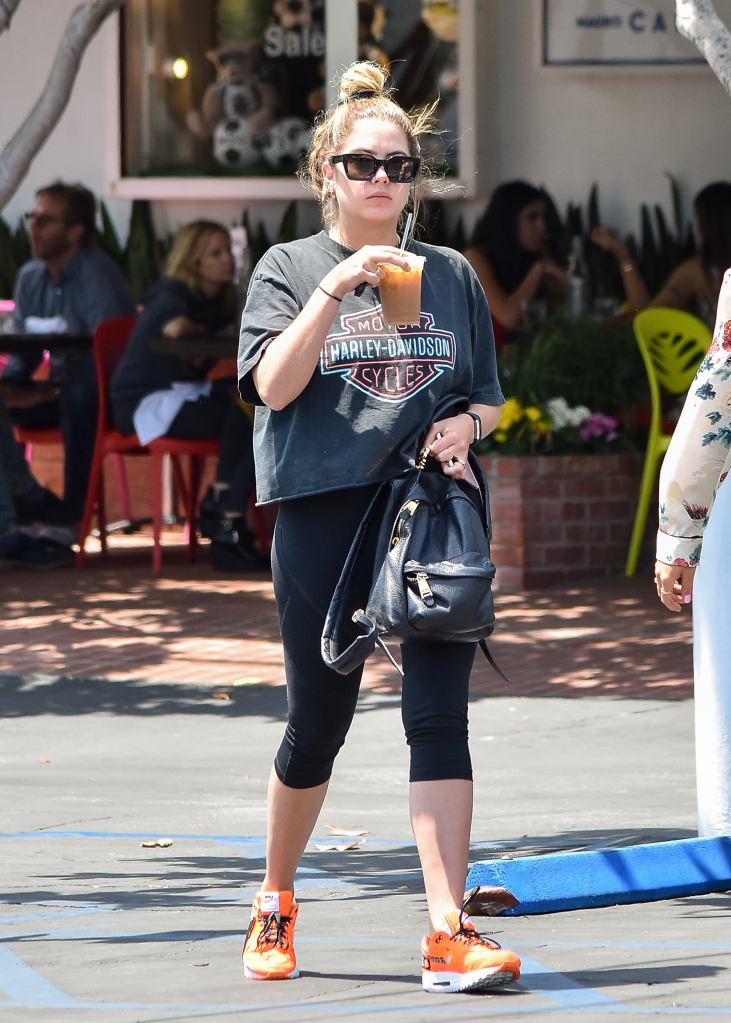 Ashley Benson gets iced coffee in a black athleisure look along with an eye-catching pair of bright orange sneakers.