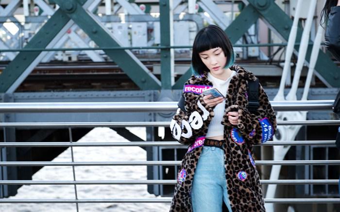 Woman in leopard coat using smartphone