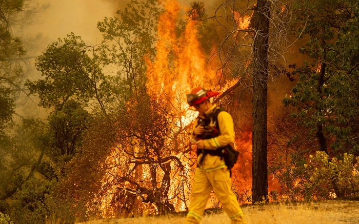 A firefighter walks near flames from the Carr Fire in Redding, Calif., onCalifornia Wildfires, Redding, USA - 28 Jul 2018