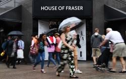 Pedestrians pass a House of Fraser