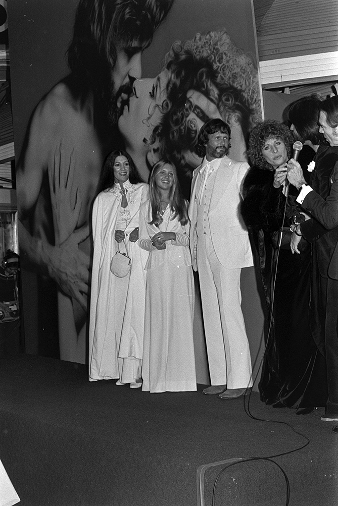 """(L-R) Rita Coolidge, Tracy Kristofferson, Kris Kristofferson, Barbra Streisand, Jon Peters, and Army Archerd attend the premiere of """"A Star Is Born"""" at Mann's Village Theater in Westwood, California, on December 18, 1976."""