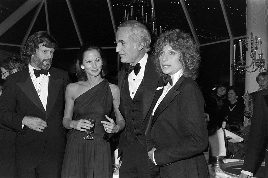 """(L-R) Kris Kristofferson, Amanda Burden, Steve Ross, and Barbra Streisand attend a party at Tavern on the Green in New York City following the New York premiere of """"A Star Is Born"""" on December 23, 1976."""