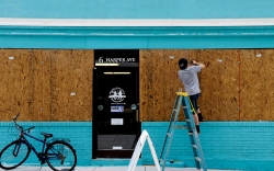A business owner boards up a