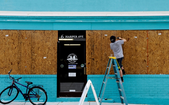A business owner boards up a storefront to prepare for Hurricane Matthew in North Carolina in October 2016