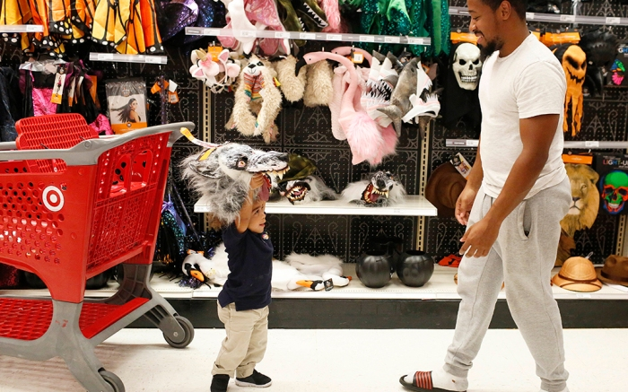 A father and son shop for Halloween costumes