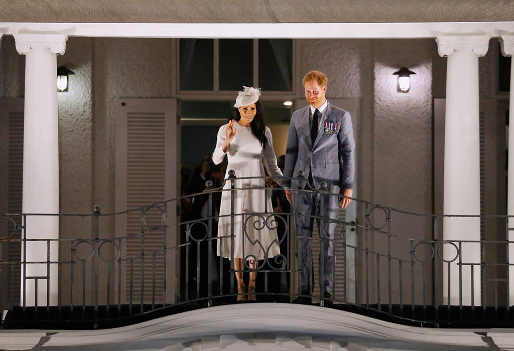 Meghan Markle and Prince Harry wave from the balcony of the Grand Pacific Hotel.