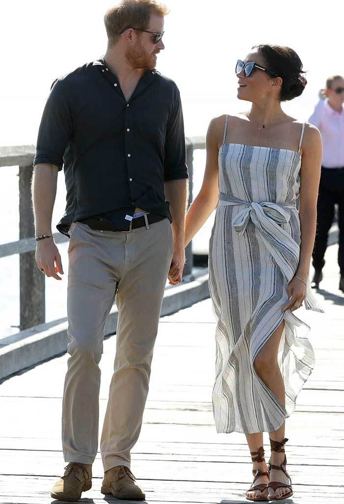 Meghan Markle wears a wrap dress by Reformation revealing a daring split when it catches the breeze.