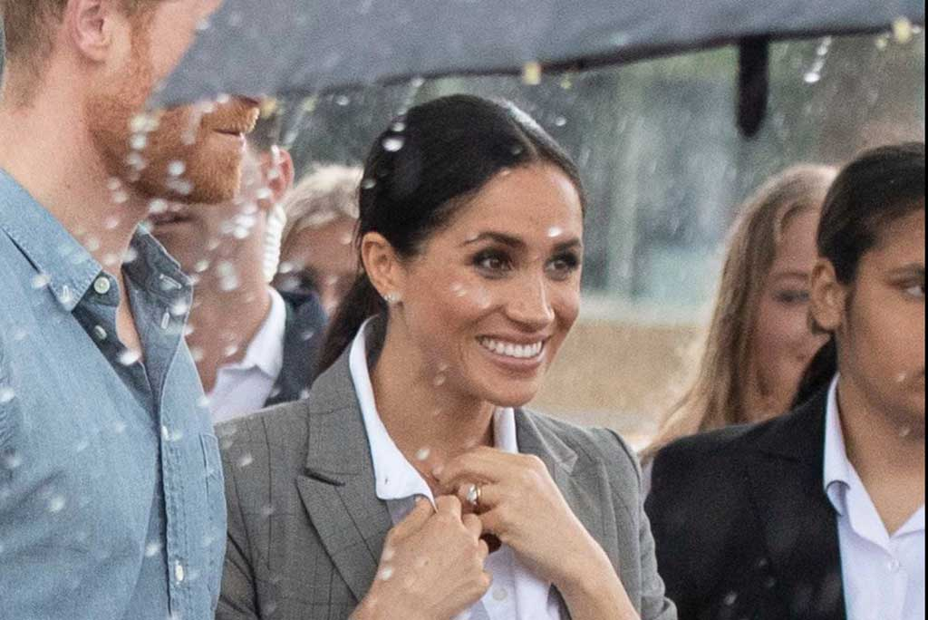 Megan Markle and Prince Harry shelter under an umbrella in the rain.