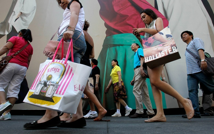 Pedestrians with shopping bags make their way along Fifth Avenue in New York. The U.S. economy grew more slowly in the summer than previously thought because consumers spent less than the government had first estimated. But economists expect growth in the current October-December quarter to be strongerEconomy, New York, USA