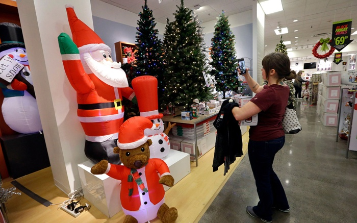 A woman takes photos of artificial Christmas trees while shopping at a JCPenney store, in Seattle. Black Friday has morphed from a single day when people got up early to score doorbusters into a whole season of deals, so shoppers may feel less need to be outHoliday Shopping Black Friday, Seattle, USA - 24 Nov 2017