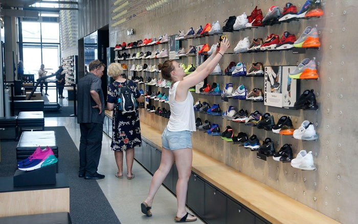 Shoppers look at shoes at the Nike Miami store on the Lincoln Road Mall, in Miami Beach, Fla. Nike's stock was falling in early trading on Tuesday following an announcement that former San Francisco 49ers quarterback Colin Kaepernick has a new deal with the athletic clothing and footwear makerKaepernick Nike, Miami Beach, USA - 04 Sep 2018
