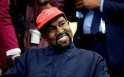 Rapper Kanye West is seated while
