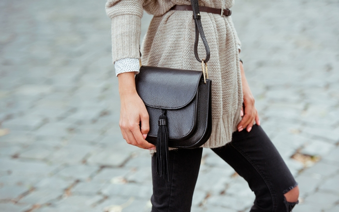 Fashionable young woman in black jeans, beige cardigan and black handbag . Street style .; Shutterstock ID 500401492; Usage (Print, Web, Both): Web; Issue Date: 11/16; Comments: web