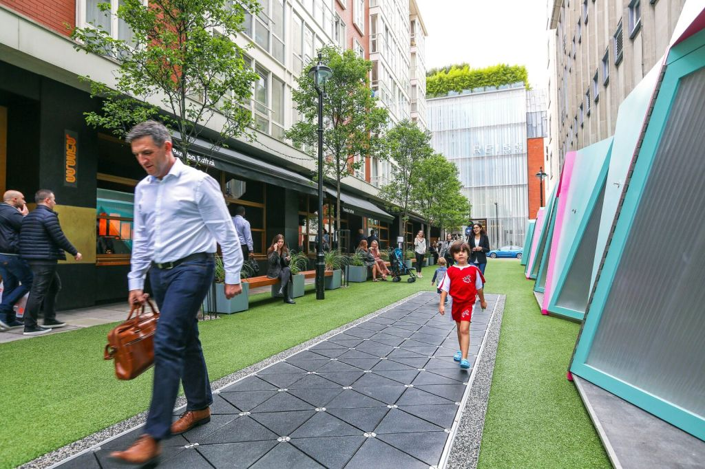 Man and child walk on Pavegen floor tiles, generating energy in an outdoor area