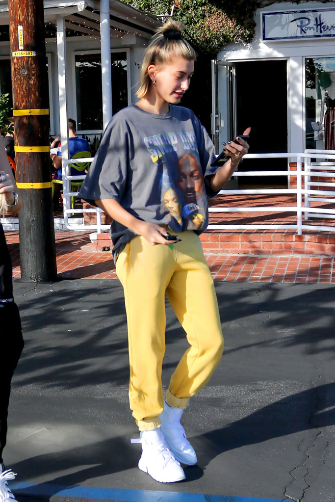 hailey baldwin, texting, snoop dogg t-shirt, yellow sweatpants, chloe, sneakers, designer, casual, street style, celebrity style