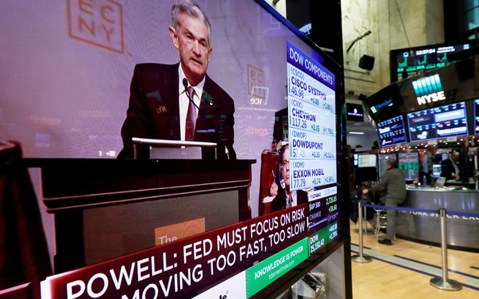 The speech of Federal Reserve Chairman Jerome Powell, to the Economic Club of New York, appears on a television screen on the floor of the New York Stock Exchange, . Powell cast a bright picture of the U.S. economy Wednesday and appeared to suggest that the Fed might consider a pause in its interest rate hikes next year to assess the impact of its credit tighteningFederal Reserve Powell, New York, USA - 28 Nov 2018