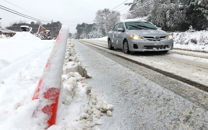 A car drives slowly down Old NC 98 in Wake Forest, N.C., on . A storm spreading snow, sleet and freezing rain across a wide swath of the South has millions of people in its path, raising the threat of immobilizing snowfalls, icy roads and possible power outagesSevere Weather North Carolina, Wake Forest, USA - 09 Dec 2018