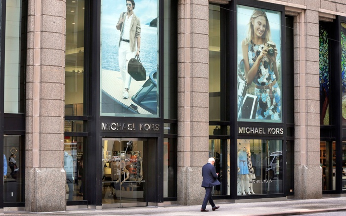 A man passes the Michael Kors store on Madison Avenue, in New York, . Michael Kors Holdings plans to close up to 125 stores over the next two years with continued weak sales at its luxury storesMichael Kors, New York, USA - 31 May 2017