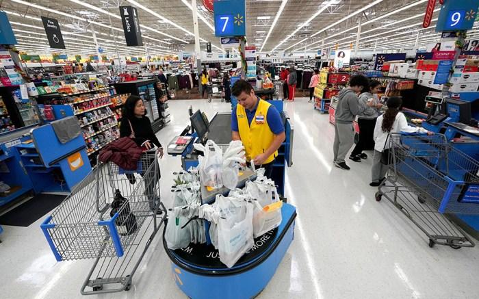 Walmart associate Luis Gutierrez, center, checks out a customer at a Walmart Supercenter, in HoustonWalmart, Houston, USA - 09 Nov 2018