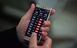 An investor watches the smartphone screen