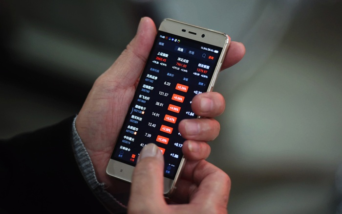 An investor watches the smartphone screen at a stock exchange hall on December 3, 2018 in Hangzhou, Zhejiang Province,China. Chinese shares rose on Monday. The Shanghai Composite Index rose 66.61 points, or 2.57 percent, to close at 2,654.80. The Shenzhen Component Index went up 256.72 points, or 3.34 percent, to close at 7,938.47 points.China stock market rise, Hangzhou, Zhejiang Province, China - 03 Dec 2018