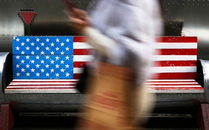 A woman walks by a bench painted with the U.S. flag at the capital city's popular shopping mall in Beijing. A U.S. delegation led by deputy U.S. trade representative, Jeffrey D. Gerrish arrived in the Chinese capital for a trade talks with China. China sounded a positive note ahead of trade talks this week with Washington, but the two sides face potentially lengthy wrangling over technology and the future of their economic relationshipUS Tariffs, Beijing, China - 06 Jan 2019