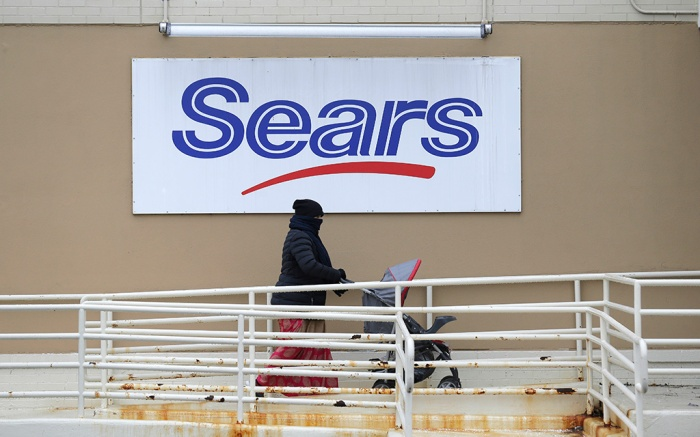 A person walks near a sign for a Sears store in Hackensack, N.J., . The iconic Sears could be heading into liquidation if its board rejects a bid by company chairman Eddie Lampert to keep the business running in its entiretySears, Hackensack, USA - 08 Jan 2019
